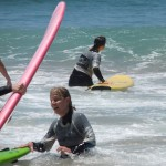 Navigating the surfboard out through slightly calmer waters, in between waves