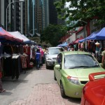 Cars drive through a street market